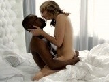 Interracial couple making love in bed